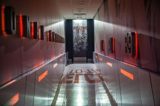 Recruits begin their journey by walking down a darkened, 60-foot corridor lined with flashing LED lights that illuminate a visual history of the Miami Hurricanes on the walls.
