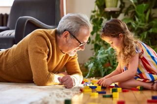 a grandfather plays blocks with granddaughter