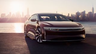 Lucid Air parked next to a river with a city skyline in the background