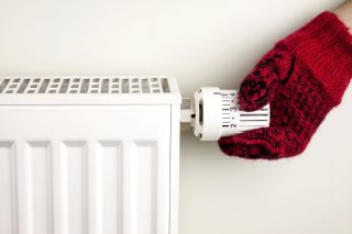 Person wearing a mitten adjusting a radiator thermostat.