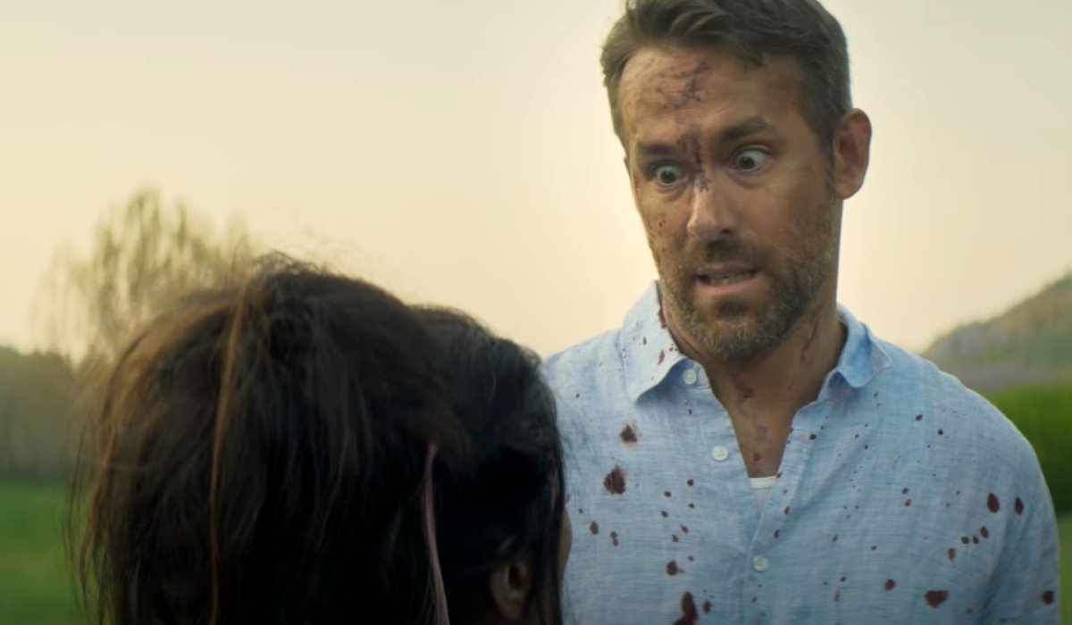 Ryan Reynolds looks horrified in a bloody shirt in The Hitman's Wife's Bodyguard.