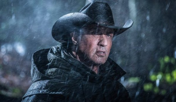 Rambo V: Last Blood John Rambo stands in the rain, with a black coat and cowboy hat