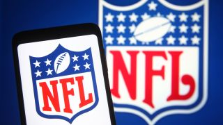 The NFL logo on a phone in front of an NFL logo in the background