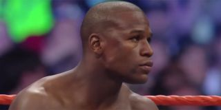 Floyd Mayweather without his shirt on getting ready to fight in a WWE ring with the crowd in the background.