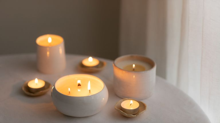 Scented candles in ceramic bowls on linen tablecloth at home