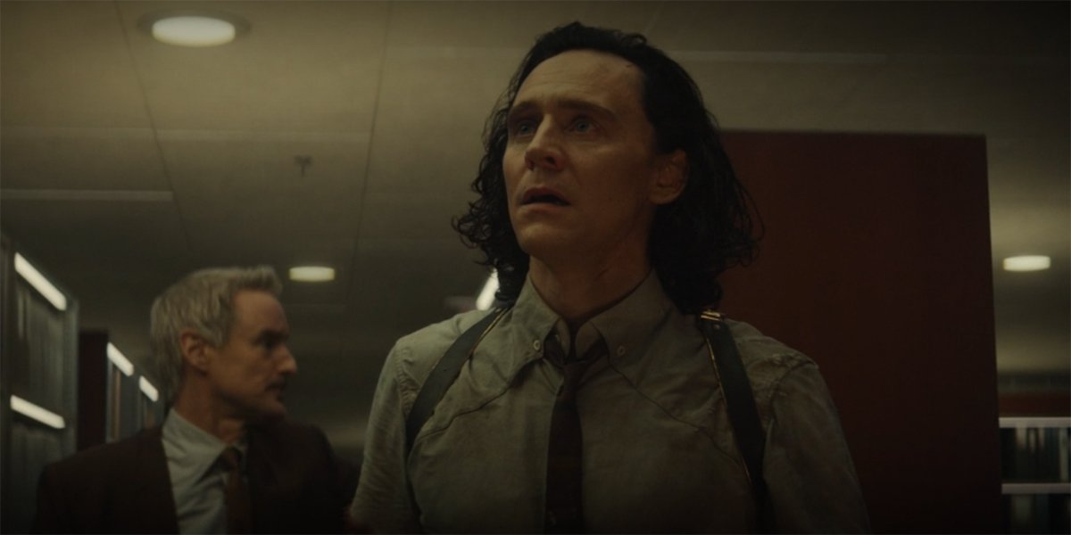 Loki looking at Kang statue