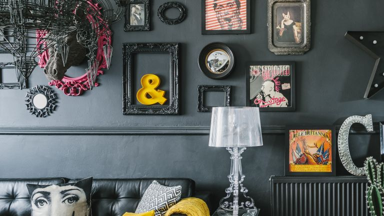 dark living room with black walls and a quirky gallery wall