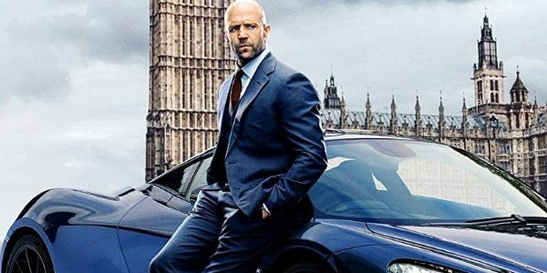 Hobbs & Shaw Deckard Shaw leaning against a Mclaren sport car in front of Parliament