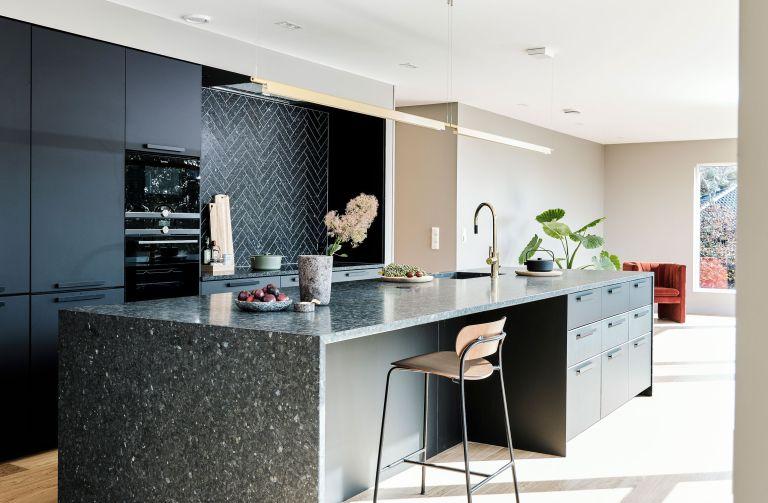 kitchen island in a large black and beige kitchen