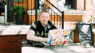 Front-end developer Wes Bos sits at a laptop at a garden table