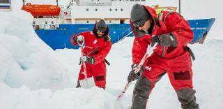 stranded icebreaker crew prepares spot for landing helicopter