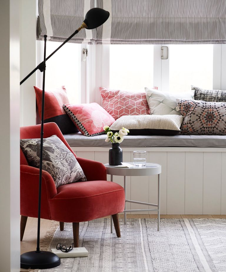 Decorating small spaces with colorful red and gray cushions, a red velvet chair and striped blinds.