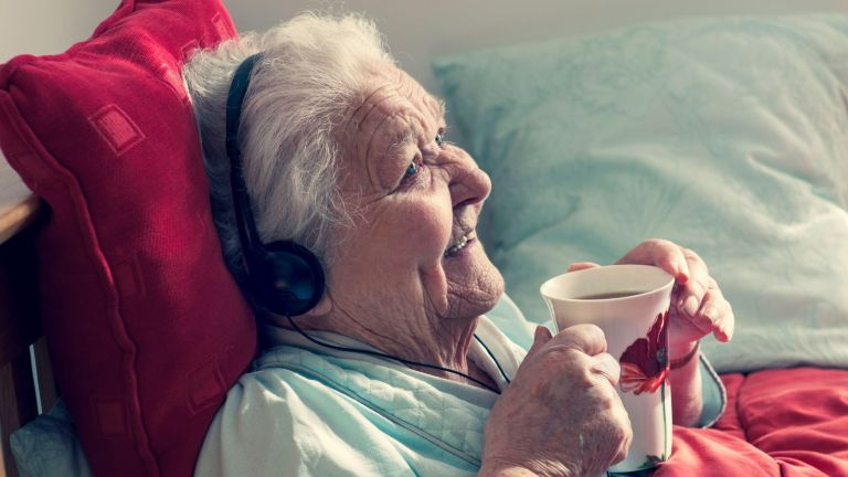 Elderly woman sat listening to music through headphones in care home