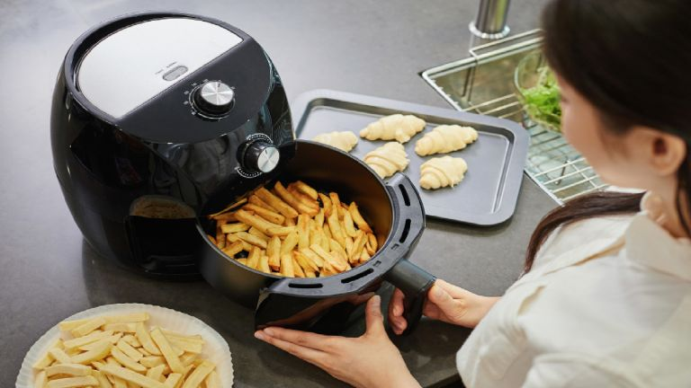 Woman using airfryer to cook chips, with other ingredients on workbench