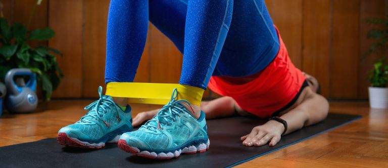 Woman exercising at home on mat with resistance band around ankles