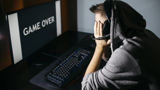Young man sitting at his PC, looking at screen with game over text