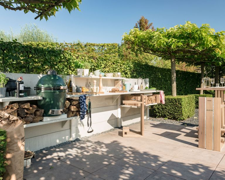 How much does an outdoor kitchen cost, illustrated by a white wooden outdoor scheme beside a tree-lined hedge.