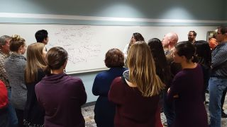 people standing around a whiteboard