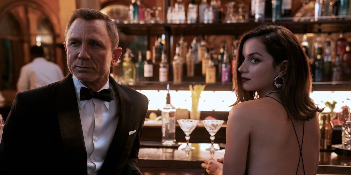 James Bond (Daniel Craig) and Paloma (Ana de Armas) sit at a bar in 'No Time To Die'