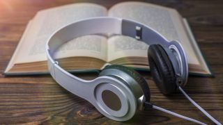 A pair of headphones resting on top of a book lying on a wooden table