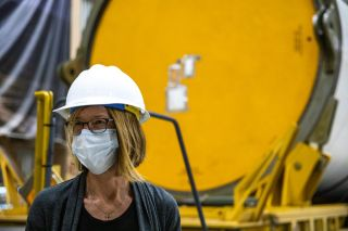 Kathy Lueders, NASA's associate administrator for Human Exploration and Operations, views Artemis hardware inside the Rotation, Processing and Surge Facility at NASA's Kennedy Space Center in Florida, on June 25, 2020. Behind her are solid rocket booster segments for NASA's new Space Launch System rocket, which the agency plans to use to send astronauts to the moon.