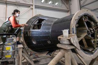A conservator uses a vacuum to clean inside Freedom 7, the first Mercury capsule to carry a U.S. astronaut into space 60 years ago, in the Mary Baker Engen Restoration Hangar at the National Air and Space Museum's Steven F. Udvar-Hazy Center.
