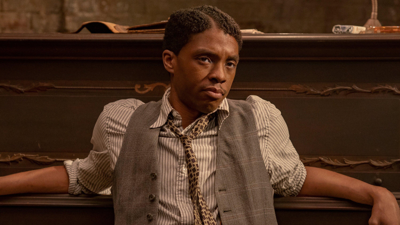 Chadwick Boseman leans back against a piano in Ma Rainey's Black Bottom.