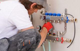 an underfloor heating manifold being installed