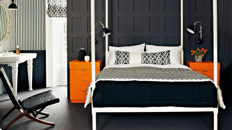 An example of dark bedrooms showing a bedroom with black panelled walls, white four poster bed and orange side tables
