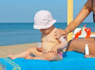 Adult putting sunscreen on a baby on the beach.