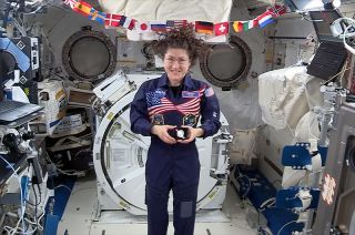 NASA astronaut Christina Koch displays a U.S. Mint Apollo 11 50th Anniversary commemorative coin on board the International Space Station in May 2019.