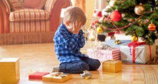 Boy crying at Christmas tree