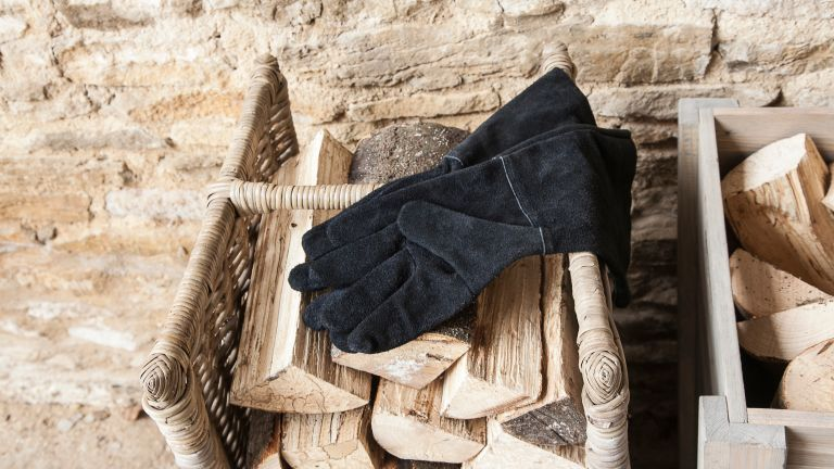 the best gardening gloves: black suede gardening gloves laid on chopped wood by gardening trading