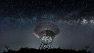 A radio telescope with the Milky Way in the background
