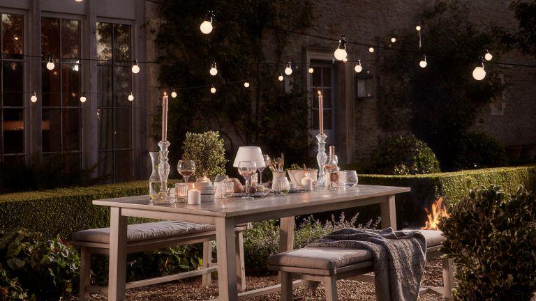 festoon light ideas: cox & cox extendable globe festoon lights over outdoor bench