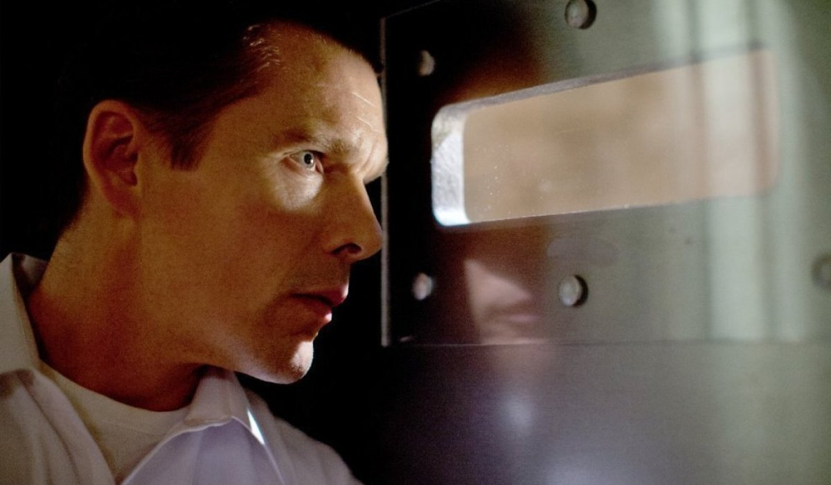 Ethan Hawke looks through a letterbox with anxiety in The Purge.