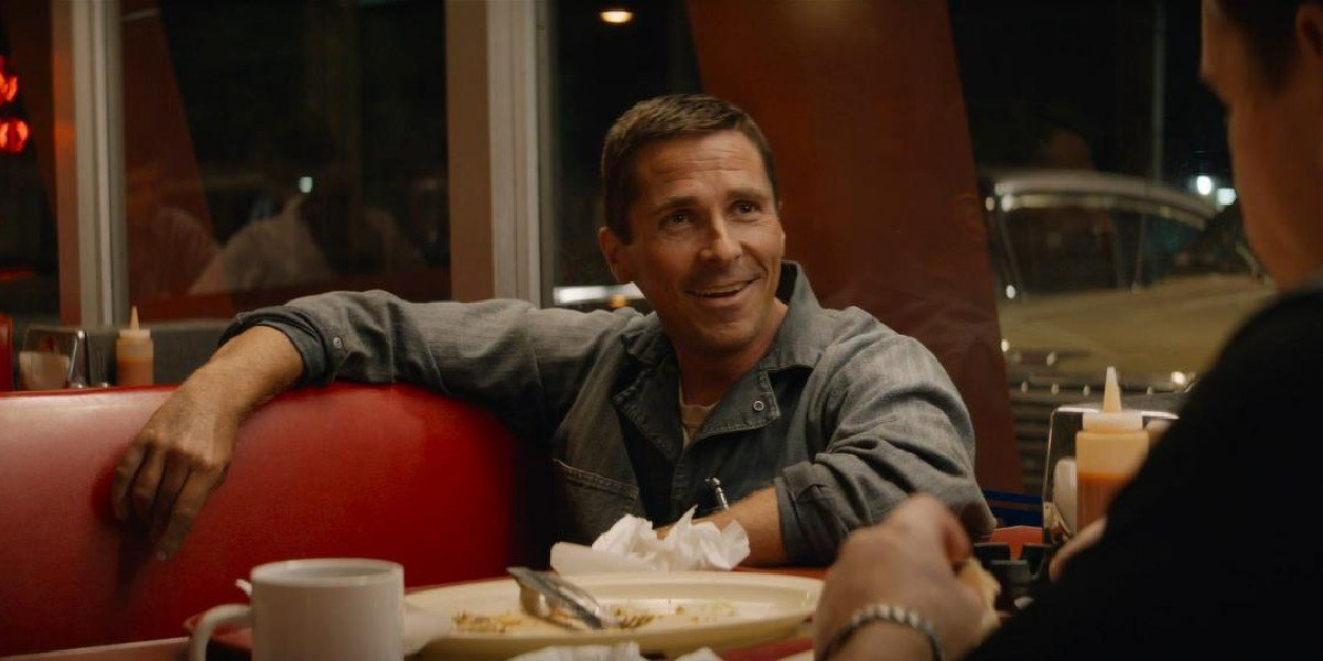 Ford v Ferrari Christian Bale smiles while sitting in a diner booth