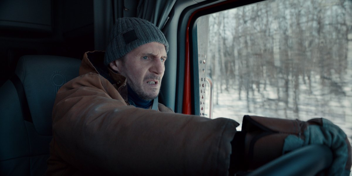 Liam Neeson driving with an intense look on his face in The Ice Road.