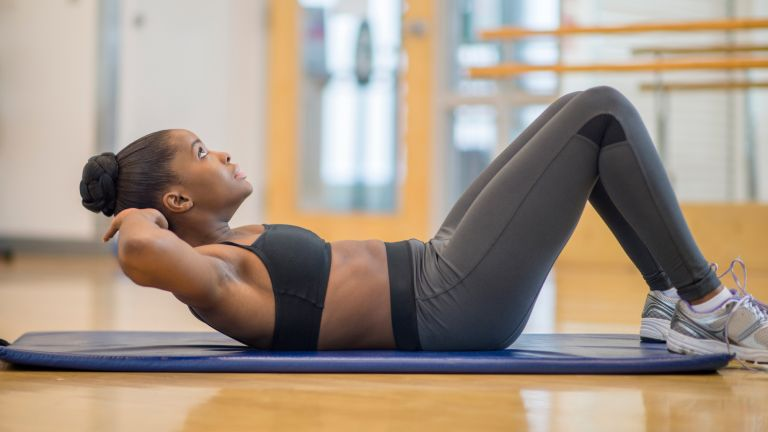 Woman doing sit-ups in a studio