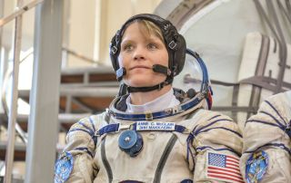 NASA astronaut Anne McClain poses in a spacesuit on Earth.