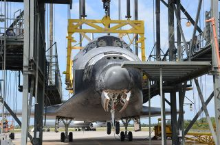 Space shuttle Discovery, suspended in Kennedy Space Center's Mate-Demate Device, was delayed a day being lifted atop its jumbo jet ride to the Smithsonian due to winds on April 14, 2012.
