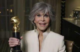 Jane Fonda holding her Golden Globe.