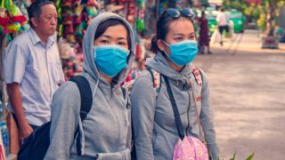 On the city street, two girls in blindfolds, the concept of the spread of the coronavirus from China, toned. E