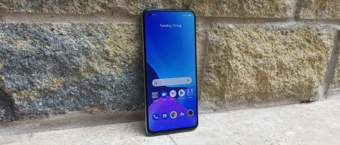 The Realme GT Master Edition facing forwards against a wall.
