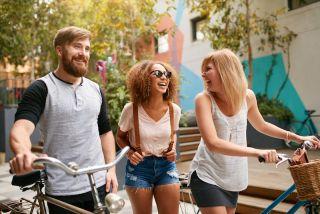 Three friends walk down a street together
