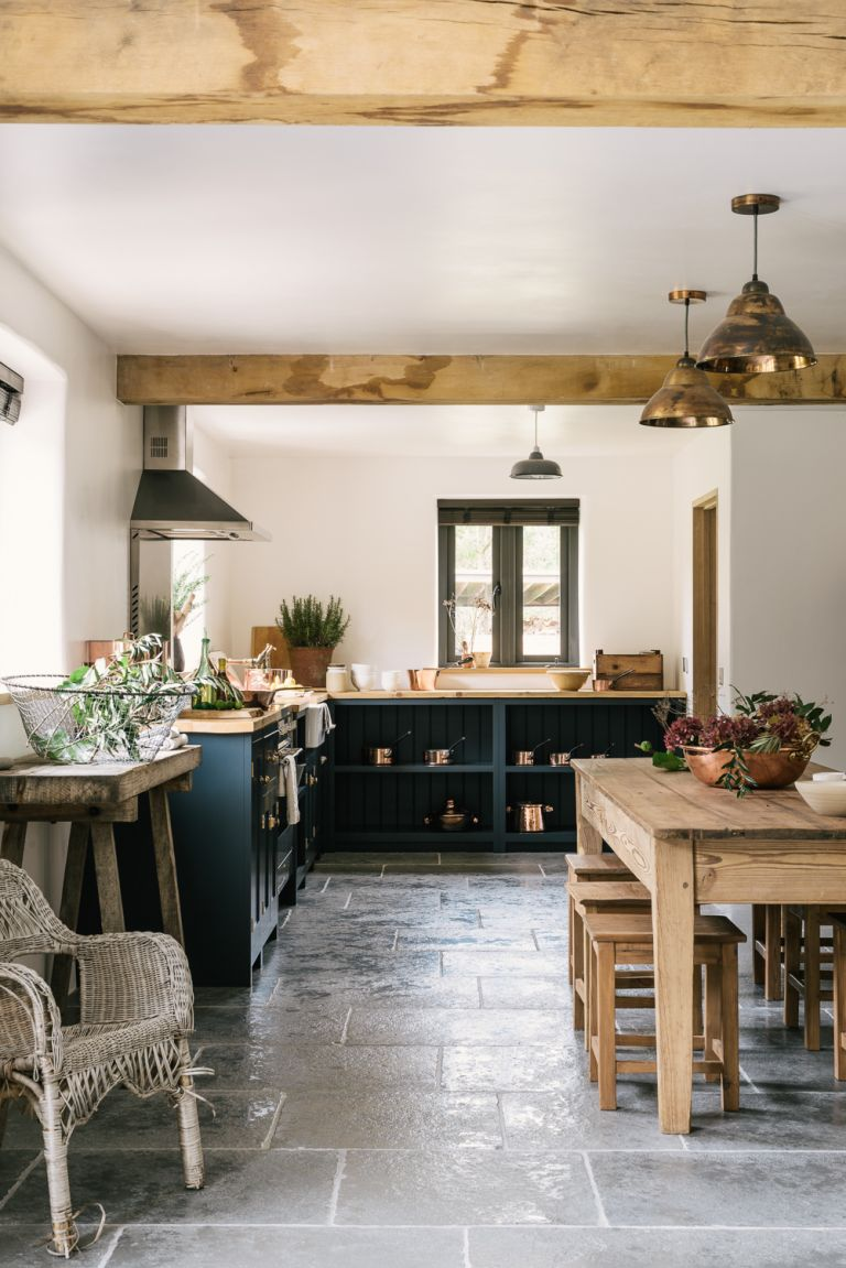 stone floor in a country kitchen with dark blue cabinets, wood dining table and wood worktops