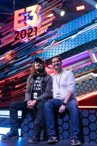 two men sitting under E3 2021 sign