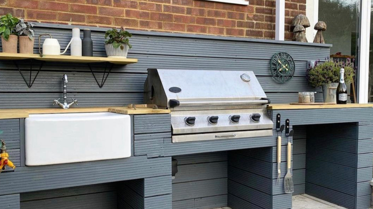 See how a couple created a stunning outdoor kitchen from an old BBQ and decking boards