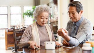 An elderly woman helps an elderly man check his blood pressure.