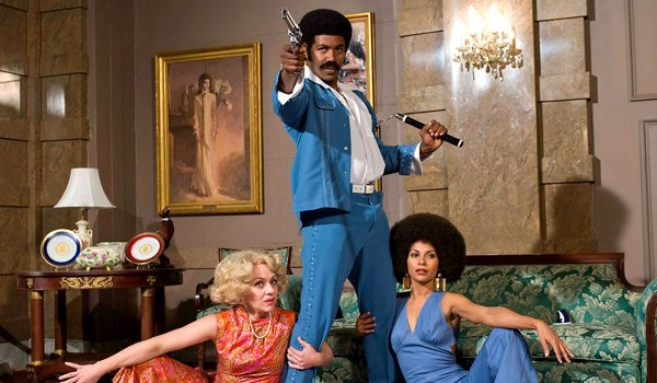 Black Dynamite poses with his gun, his nunchucks, and some ladies
